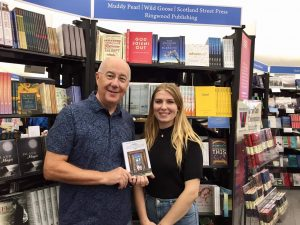 Proud author and AMD Harley Griffiths cradle Gerry's new book